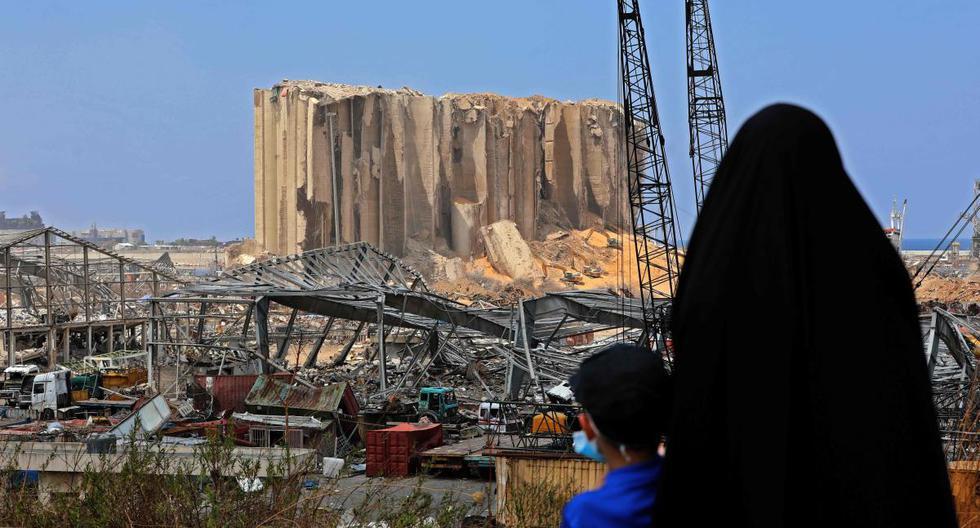 Una mujer con su niño contempla este miércoles 12 de agosto de 2020 los silos de grano dañados en el puerto de Beirut (Líbano).  (AFP / Anwar AMRO).