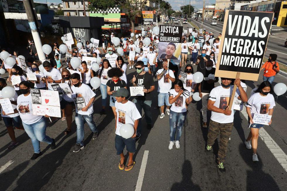 La marcha, que reunió a unas 250 personas, contó con numerosos carteles de denuncia al racismo y contra la violencia policial. Amigos del adolescente, identificado como Guilherme Silva Guedes, caminaron en silencio portando velas en señal de luto. (EFE/Leo Barrilari).