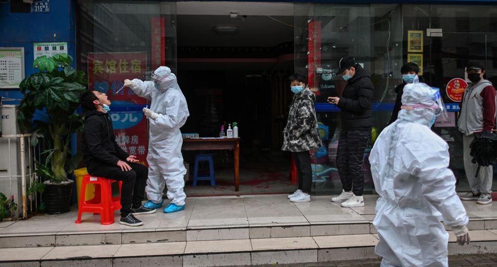 Las personas esperan en la fila mientras un trabajador médico toma una muestra con un hisopo de una persona para analizar si es portador del nuevo coronavirus en Wuhan, provincia central de Hubei, China. (Foto: AFP/Héctor Retamal)