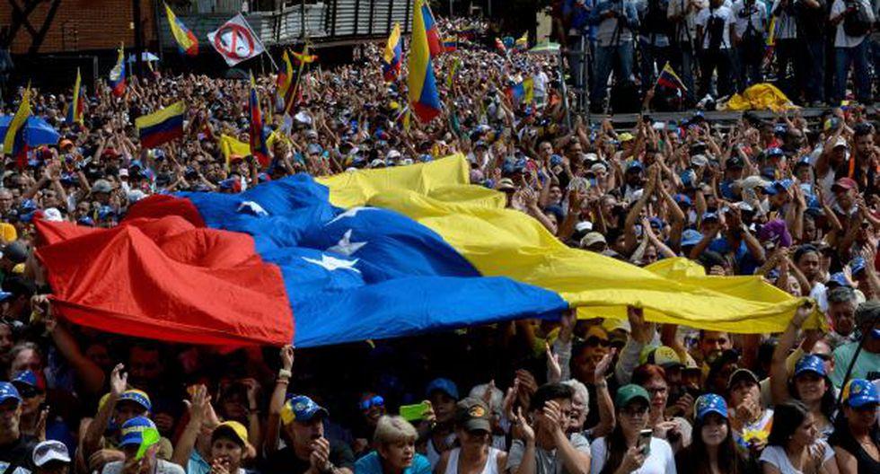 """La gente escucha al jefe de la Asamblea Nacional de Venezuela, Juan Guaido, durante un mitin de oposición en masa contra el líder Nicolás Maduro, en el que se declaró a sí mismo el """"presidente interino"""" del país. (Foto: AFP)"""