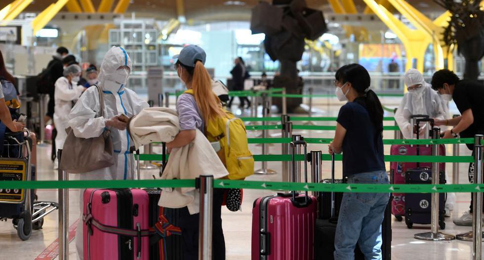 Un pasajero con un traje de protección espera para registrarse para un vuelo con destino a Beijing en el aeropuerto de Barajas en Madrid el 20 de junio de 2020. (Foto de PIERRE-PHILIPPE MARCOU / AFP).