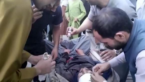 En esta toma de fotograma del video, las personas atienden a un hombre herido cerca del lugar de una explosión mortal afuera del aeropuerto en Kabul, Afganistán, el jueves 26 de agosto de 2021. (Foto AP).