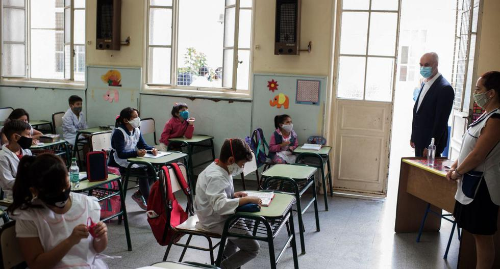 Imagen muestra al alcalde Horacio Rodríguez Larreta (2-derecha) mirando a los niños mientras asisten a clases en una escuela pública en Buenos Aires, Argentina, el 17 de febrero de 2021. (WALTER CARRERA / BUENOS AIRES CITY GOVERNMENT / AFP).