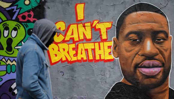 Imagen referencial. Un hombre camina junto a un graffiti en una pared que representa un retrato de George Floyd, un hombre afroestadounidense que murió en Minneapolis a manos de la policía. (David GANNON / AFP)