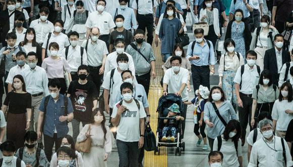 Los viajeros usan mascarillas en una estación de tren en Tokio, Japón, el 28 de julio de 2021. (Foto de Yasuyoshi CHIBA / AFP).