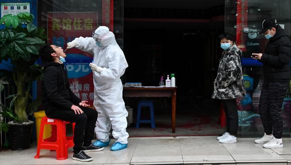 Esta foto muestra a personas esperando en la fila mientras un trabajador médico toma una muestra de hisopo de una persona para analizar el nuevo coronavirus en Wuhan, en el centro de China Provincia de Hubei, un día después de que las restricciones de viaje a la ciudad se aliviaran después del brote. (Foto: AFP/Hector Retamal)