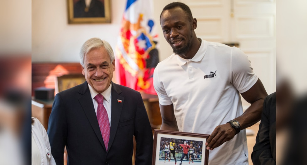 Usain Bolt posa junto al mandatario Sebastián Piñera y su curioso obsequio. (Foto: AFP)