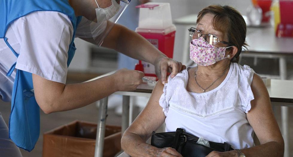 Un trabajador de salud aplica una dosis de la vacuna Sputnik V contra COVID-19 a una señora en Ezeiza, a las afueras de Buenos Aires (Argentina). (JUAN MABROMATA / AFP).