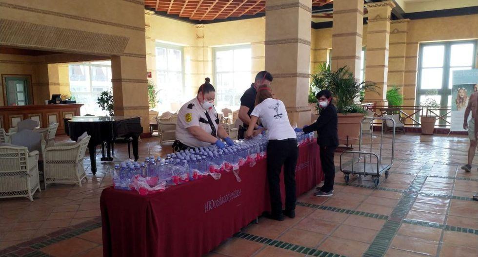 Empleados colocan botellas de agua  sobre una mesa en el hotel de Tenerife tras confirmarse caso de coronavirus. (Reuters).
