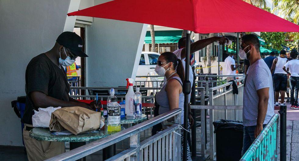 Imagen referencial. Una pareja ingresa a un restaurante en Miami. (AFP / CHANDAN KHANNA).