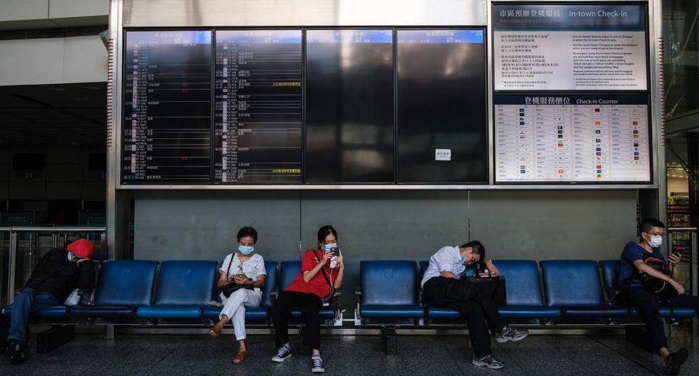 Las personas usan máscaras faciales mientras se sientan debajo de un tablero de salida de vuelos en el aeropuerto internacional de Hong Kong, el 16 de julio de 2020. (Anthony WALLACE / AFP).