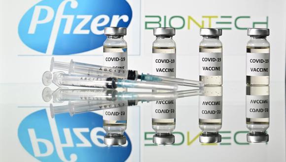 En esta foto de archivo tomada el 17 de noviembre de 2020 muestra viales con adhesivos de la vacuna Covid-19 adheridos y jeringas con el logotipo de la compañía farmacéutica estadounidense Pfizer y el socio alemán BioNTech. (Foto de JUSTIN TALLIS / AFP).