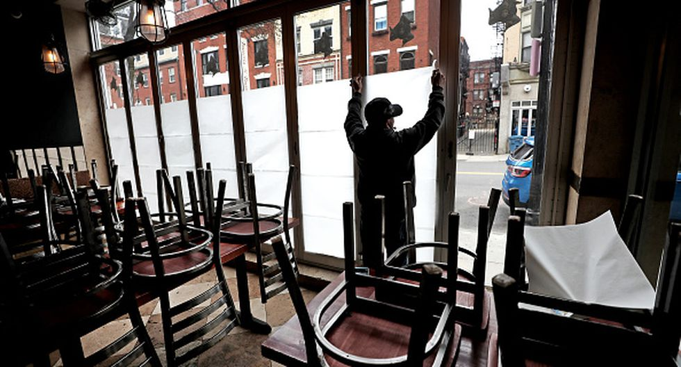 BOSTON, MA - MARCH 25: An employee of Carmelina's in the North End of Boston tapes up paper in the windows of the restaurant, which is temporarily closing during the coronavirus pandemic, on March 25, 2020. Gov. Charlie Baker ordered all nonessential businesses to close, but restaurants could stay open for deliveries. (Photo by David L. Ryan/The Boston Globe via Getty Images)