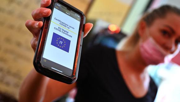 Un cliente muestra su Green Pass en un teléfono móvil en un bar del centro de Roma el 6 de agosto de 2021, cuando Italia lo hizo requerido para ingresar a cines, museos y para comer en el interior de los restaurantes. (Foto: Andreas SOLARO / AFP)