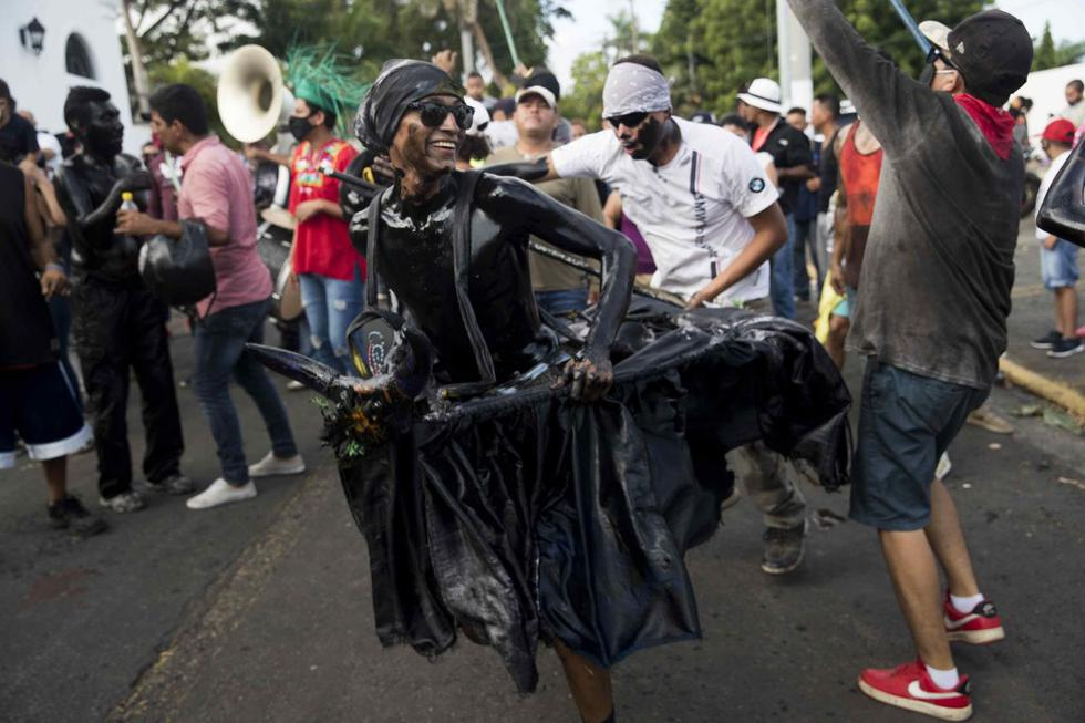 Un hombre (centro) realiza un tradicional baile durante una procesión en honor a Santo Domingo de Guzmán en Managua (Nicaragua). (EFE/ Jorge Torres).