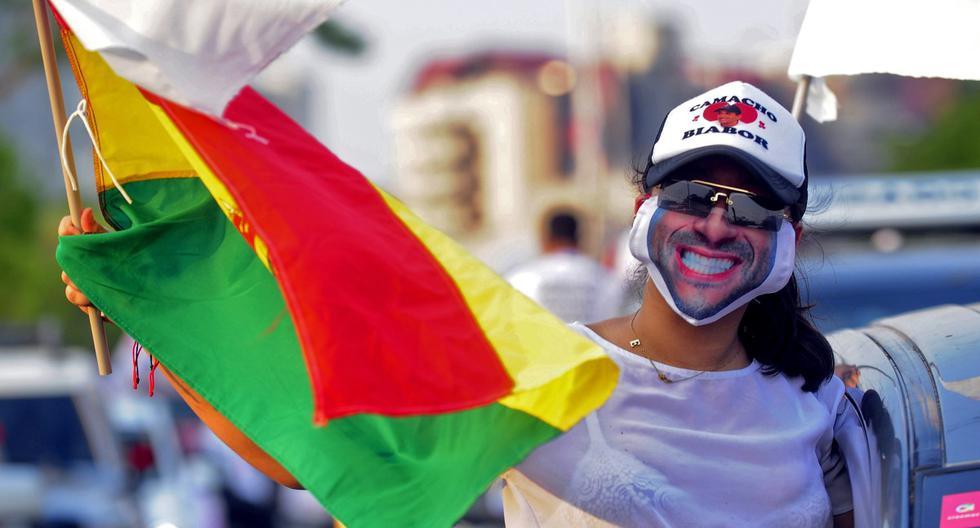 Imagen referencial. Un partidario del candidato presidencial  Luis Fernando Camacho usa una máscara que lo representa y ondea una bandera boliviana durante el mitin de clausura de su campaña en Santa Cruz, Bolivia. (Enrique CANEDO / AFP).