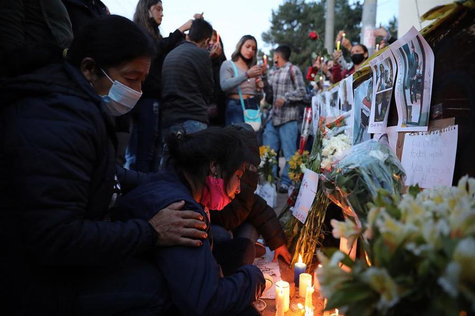 En un improvisado altar, levantado en una calle en donde está un cuartelillo de la Policía, familiares y amigos pusieron fotos de los difuntos mientras otros repartían flores, velas y oraban. (Foto: EFE/ Carlos Ortega)