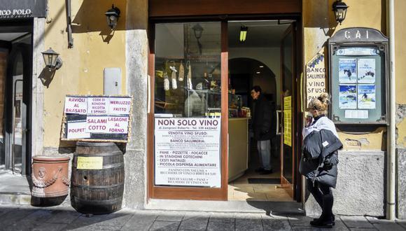 Una mujer pasa junto a una tienda abierta en la ciudad de Codogno, en la región de Lombardia, norte de Italia. (Claudio Furlan / LaPresse vía AP).