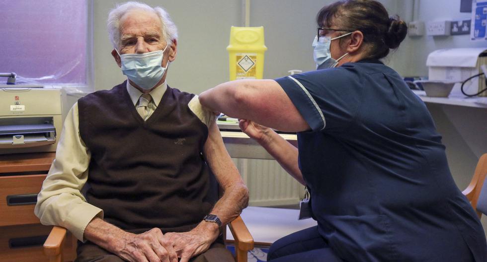 El paciente Brian Horne recibe una dosis de la vacuna Pfizer-BioNtech COVID-19 de la enfermera principal Helen Ellis Steve en el oeste de Londres, Reino Unido, el 14 de diciembre de 2020. (Steve Parsons / POOL / AFP).