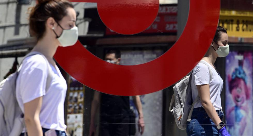 Una mujer con máscara y guantes se refleja en un espejo mientras camina en Madrid (España), el 21 de mayo de 2020. (JAVIER SORIANO / AFP).