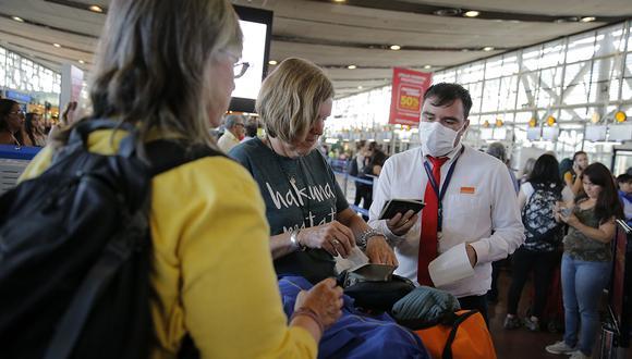 Miembro del personal de una aerolínea usa máscara protectora como medida preventiva contra la propagación del coronavirus COVID-19, en el Aeropuerto Internacional Arturo Merino Benítez, en Santiago. (Foto: AFP)