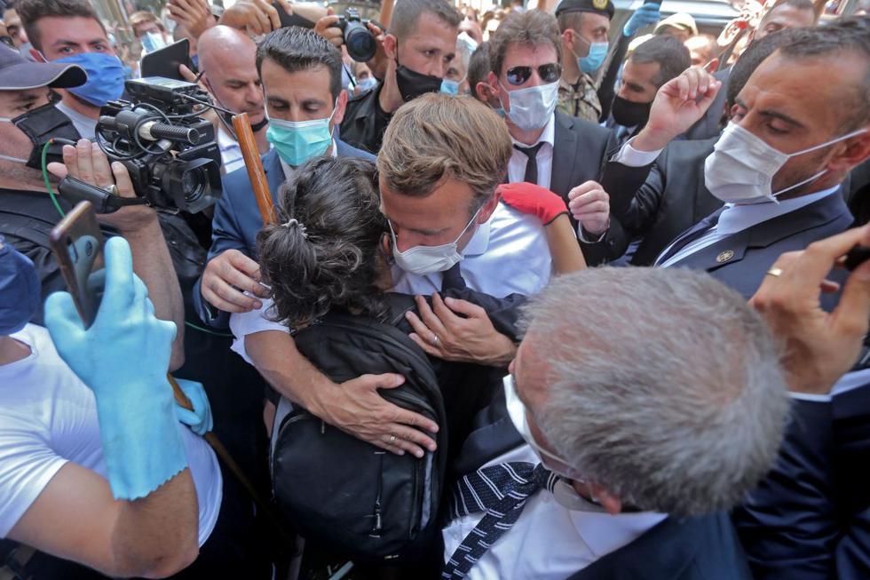 Una joven libanés abraza al presidente francés Emmanuel Macron durante una visita al vecindario de Gemmayzeh en Beirut. (AFP).