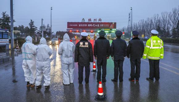 Miembros del personal médico que usan ropa protectora para ayudar a detener la propagación de un virus mortal que comenzó en Wuhan, haciendo guardia con agentes de policía en un punto de control de autopistas en Tengzhou, en la provincia oriental china de Shandong. (Foto: AFP)