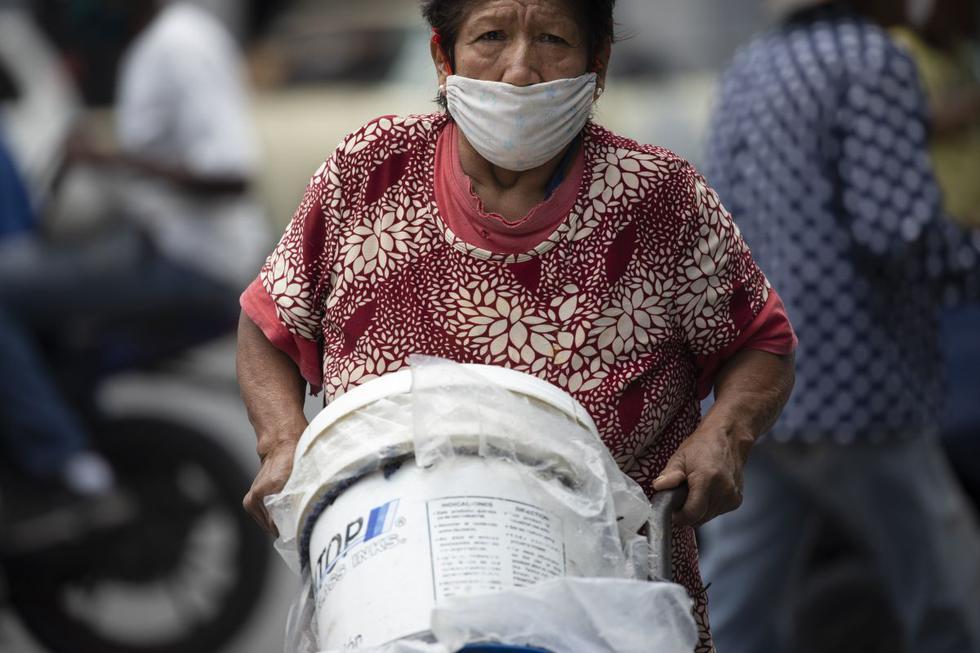 Una mujer, con una máscara facial protectora, empuja una carretilla de contenedores llenos de agua, en Caracas. (AP Photo/Ariana Cubillos).