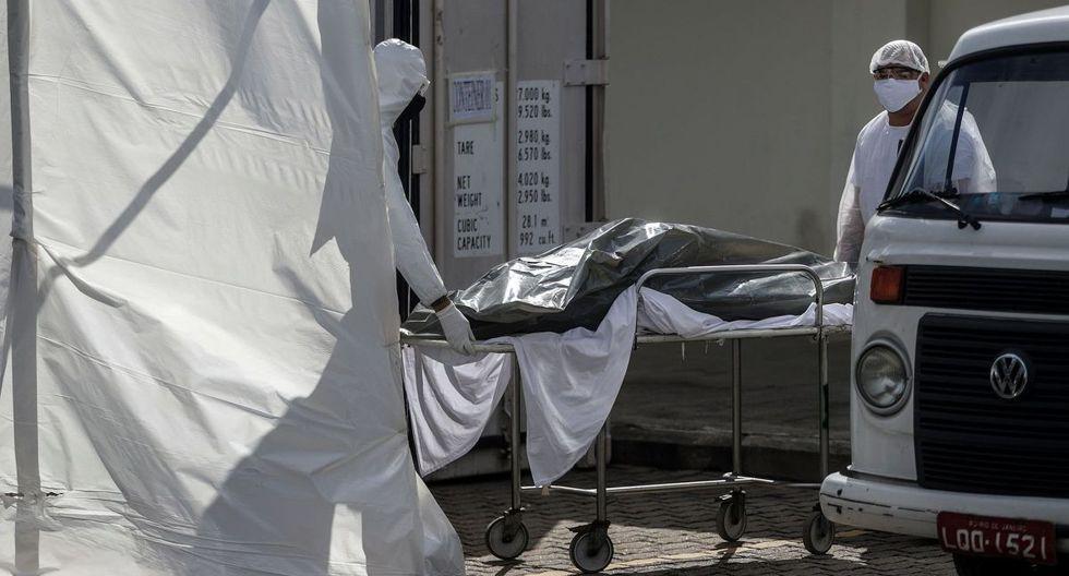Empleados de una empresa funeraria retiran de un frigorífico el cuerpo de un hombre que murió al parecer por COVID-19 el pasado viernes 8 de mayo en Río de Janeiro, Brasil. (EFE/Antonio Lacerda).