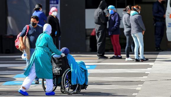 Familiares de pacientes diagnosticados con COVID-19 esperan información mientras ingresa un paciente en silla de ruedas. (EFE/José Jácome).