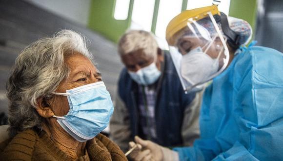 Un trabajador de salud inocula una dosis de la vacuna Pfizer-BioNTech contra COVID-19 a una persona mayor, en un centro de vacunación en Lima el 23 de abril de 2021. (Foto: ERNESTO BENAVIDES / AFP)