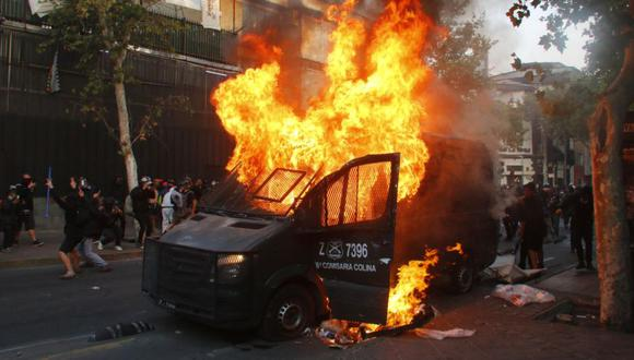 Fotografía de un vehículo de Carabineros en llamas durante una manifestación en la Plaza Italia de Santiago (Chile). (EFE/Sebastián Silva).