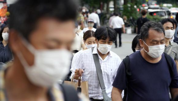 Los peatones que llevan mascarillas por el coronavirus caminan en una calle del distrito de Shinjuku en Tokio, Japón. (EFE/EPA/FRANCK ROBICHON).