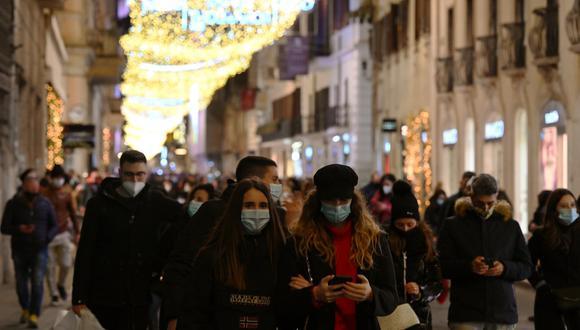 Personas con máscara facial recorren la calle principal Vía del Corso en el centro de Roma, para sus compras navideñas en medio de la pandemia de COVID-19. (Foto de Vincenzo PINTO / AFP)