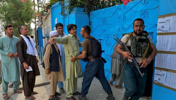 El 28 de septiembre de 2019, un personal de la fuerza de seguridad revisa a un hombre frente a una mesa electoral en Jalalabad. (Foto: AFP)