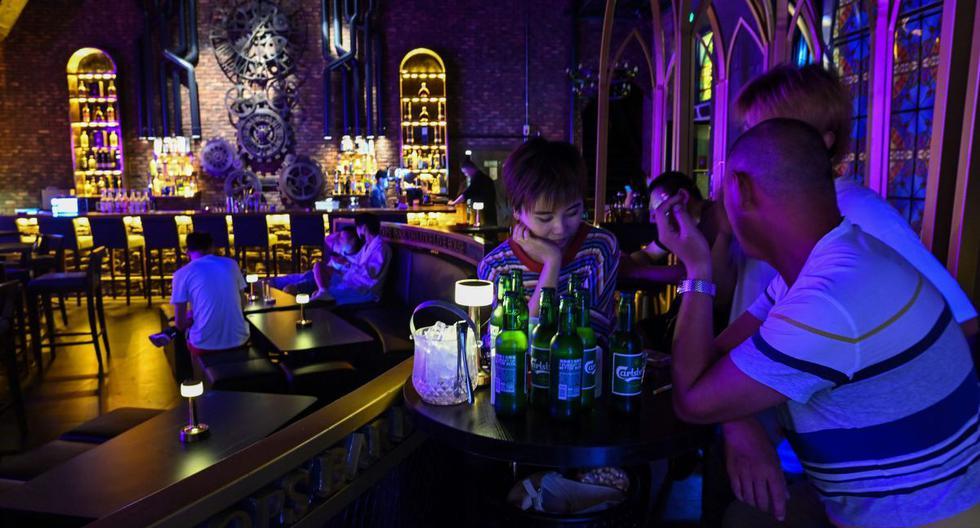 Personas sin mascarillas son captadas en un bar de la ciudad de Wuhan, provincia central de Hubei, China. (AFP / Hector RETAMAL).