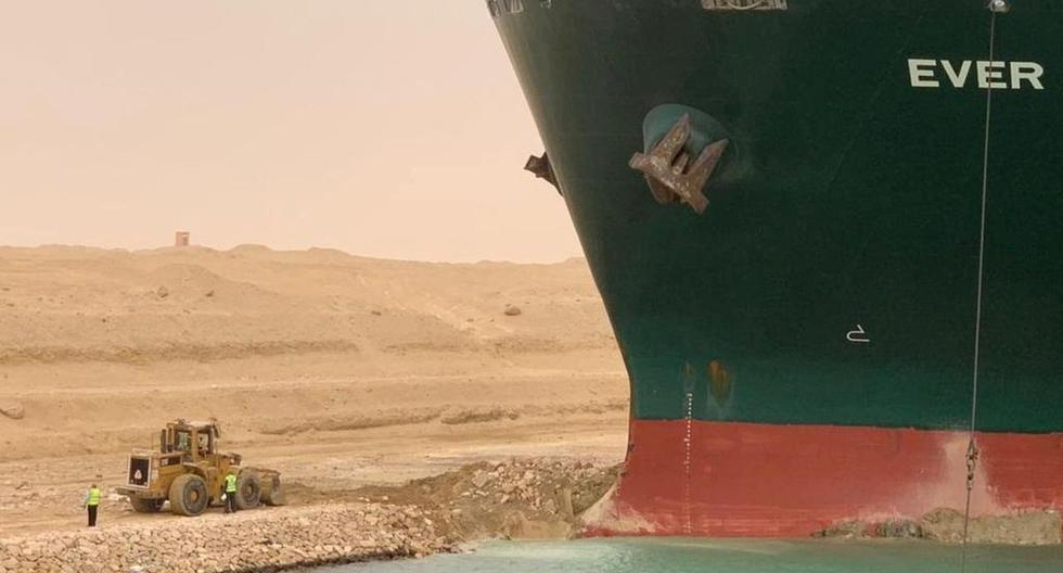 Se ve a los trabajadores junto a un buque portacontenedores que fue golpeado por un fuerte viento y encalló en el Canal de Suez, Egipto, el 24 de marzo de 2021. (Suez Canal Authority/REUTERS).