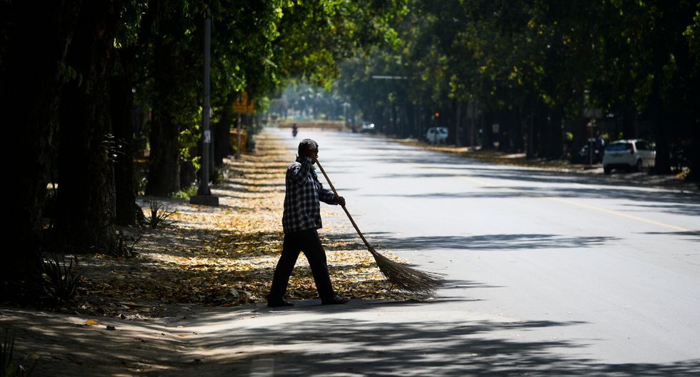 Un hombre que lleva una máscara de protección barre una calle desierta de Nueva Delhi durante el primer día de bloqueo nacional por coronavirus en India. (AFP).