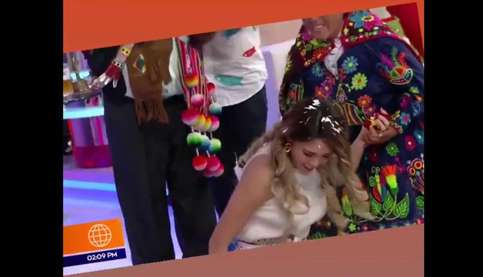 Sheyla Rojas se da un baño de florecimiento para el Año Nuevo, pero resbala y cae al piso. (América TV)