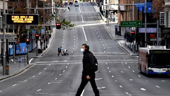 Un hombre camina por la carretera principal en el distrito comercial central de Sídney. (Saeed KHAN / AFP).