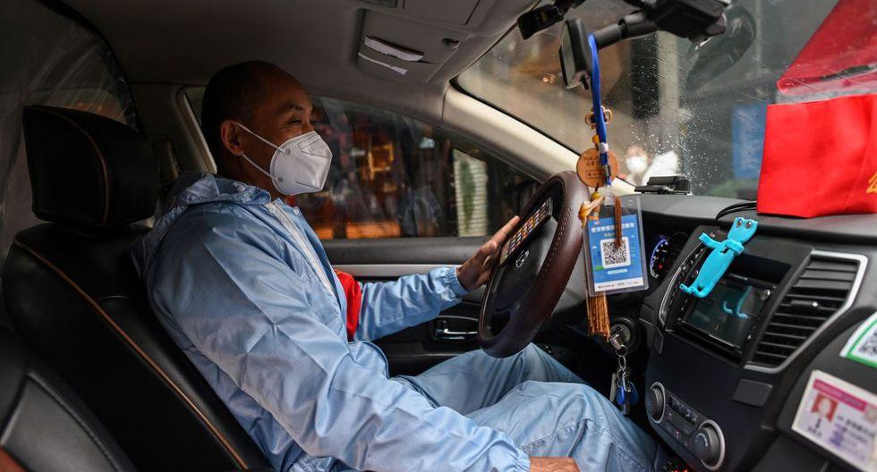 Un taxista, vestido con un traje protector y una sábana de plástico que se separa de los pasajeros como medida preventiva contra el coronavirus, se sienta en su vehículo en Wuhan, la provincia central de Hubei de China. (Foto: AFP/Héctor Retamal)