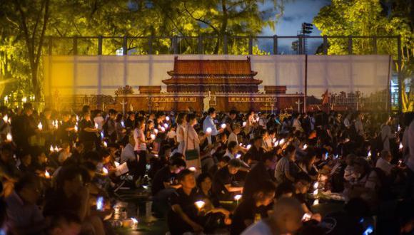 La gente sostiene velas frente a un telón de fondo que muestra la Plaza Tiananmen de Pekín durante una vigilia en Hong Kong el 4 de junio de 2018. (Foto: AFP)