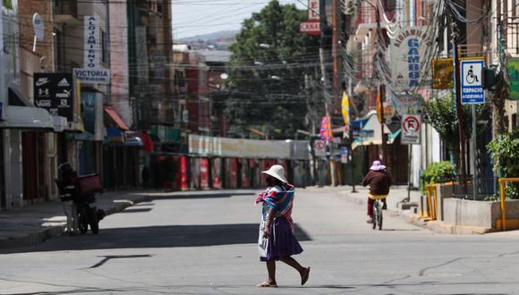 Ciudadanos circulan hoy por una avenida casi vacía, durante la cuarentena estricta dadas las fechas festivas del carnaval en Cochabamba (Bolivia). (EFE/Martín Alipaz).