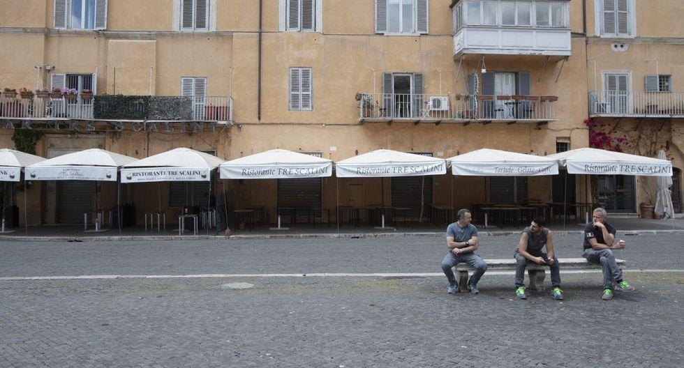 Las personas se sientan frente a un restaurante cerrado en la Piazza Navona Square, en Roma. (AP/Alessandra Tarantino).