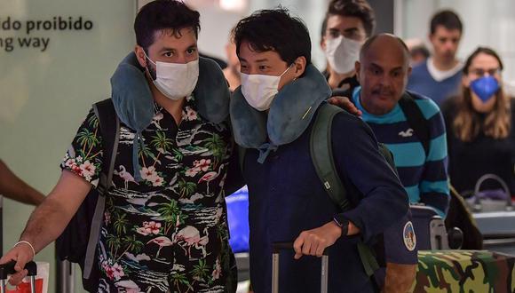 Los pasajeros que usan máscaras como medida de precaución para evitar contraer el nuevo coronavirus, COVID-19, llegan en un vuelo desde Italia al aeropuerto internacional de Guarulhos, en Guarulhos, Sao Paulo, Brasil. (Foto: AFP)