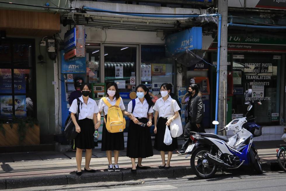 Estudiantes que usan máscaras faciales contra el coronavirus  se preparan para cruzar la calle en Bangkok, Tailandia. (EFE/EPA/DIEGO AZUBEL).