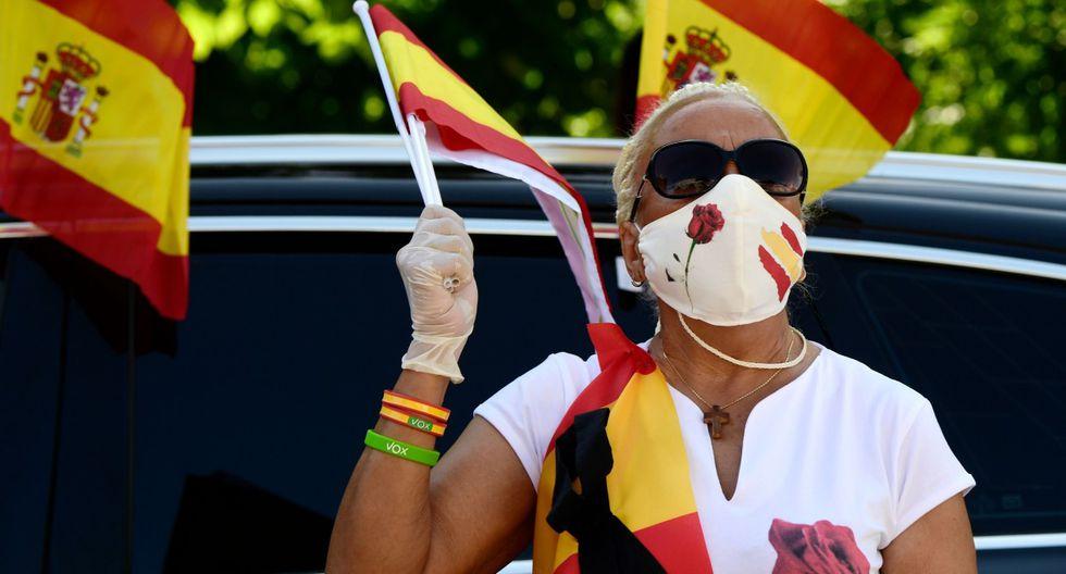 Una mujer, que usa una máscara facial por el coronavirus, ondea una bandera española en la Plaza de Colón en Madrid. (AFP / JAVIER SORIANO).