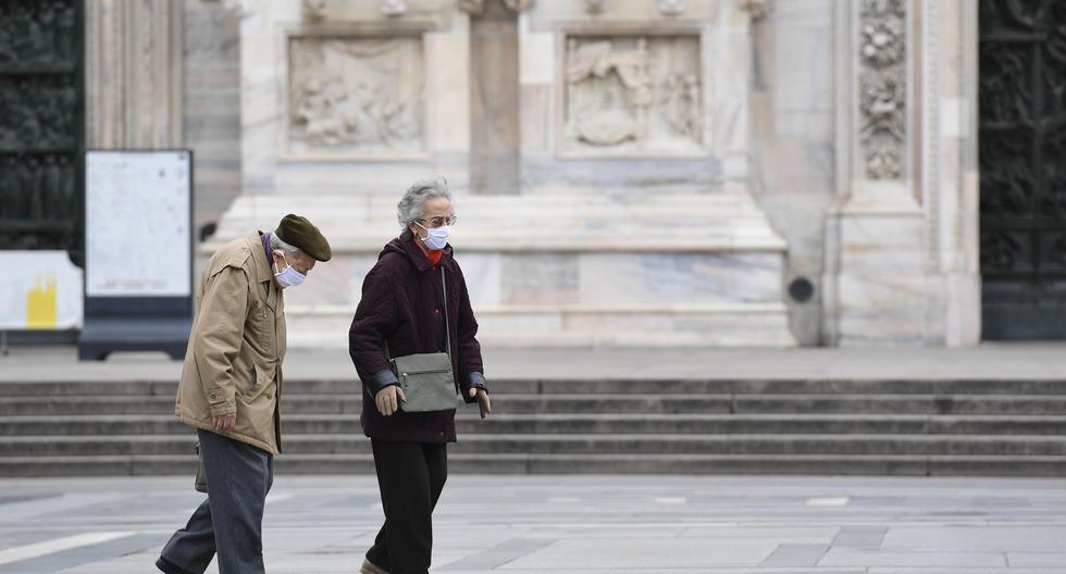 Imagen referencial. Dos personas caminan en Milán, Italia, durante el confinamiento por el COVID-19. (MIGUEL MEDINA / AFP).