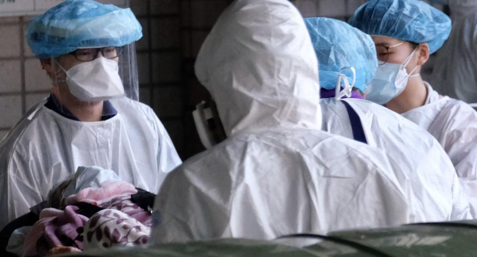 El personal médico enmascarado escolta a un paciente fuera del Hospital General de Taoyuan, donde se detectó un grupo de infecciones por coronavirus Covid-19, en Taoyuan, Taiwán, el 19 de enero de 2021. (Sam Yeh / AFP).