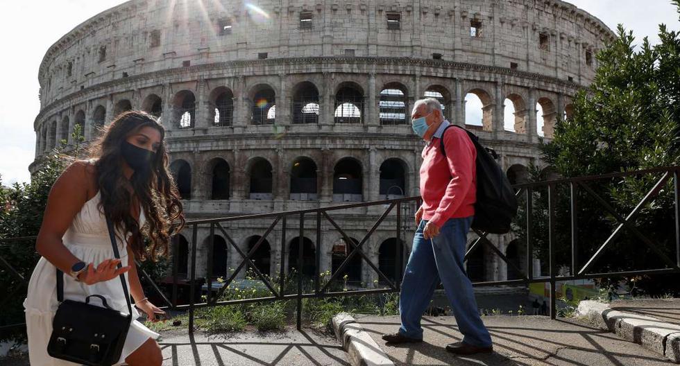 Personas que usan mascarillas pasan por el Coliseo en Roma, Italia. Foto referencial del 13 de octubre de 2020. (REUTERS/Guglielmo Mangiapane).